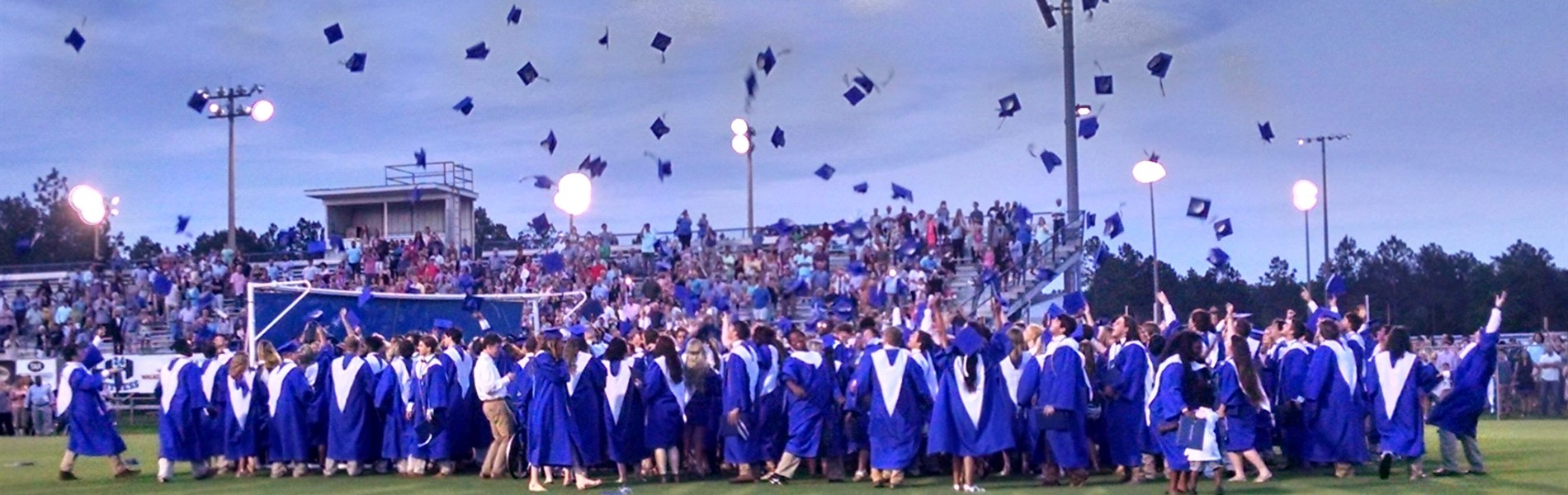 Pierce County High School graduates throwing graduation caps in the air